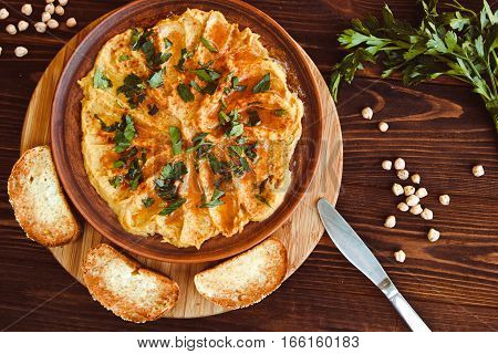 Fresh Bowl Of Homemade Hummus With Chickpeas, Olive Oil And Parsley. Served With Croutons And Nuts