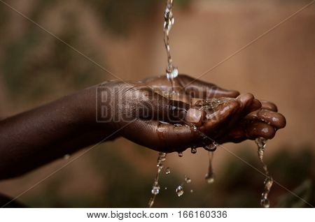 Social Issues: Water Pouring in African Childs Hands