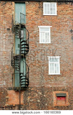 Old red brick building with fire escape stairs and windows.