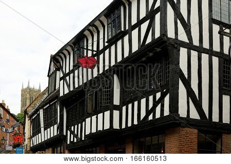 LINCOLN, UK - JULY 1, 2016: Grade II Listed timber framed medieval building on High street housing the Cardinal's Hat pub.