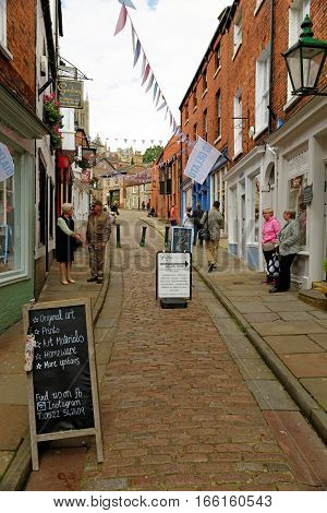 LINCOLN, UK - JULY 1, 2016: Shops lining Strait street leading to Steep Hill and the Cathedral in the historic quarter of Lincoln City Centre Lincolnshire.