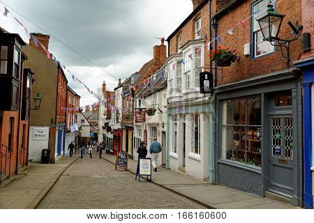 LINCOLN, UK - JULY 1, 2016: Shops lining Strait street leading to High street in the historic quarter of Lincoln City Centre Lincolnshire.