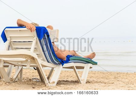 Young woman reading a book lying on deck chair at the beach