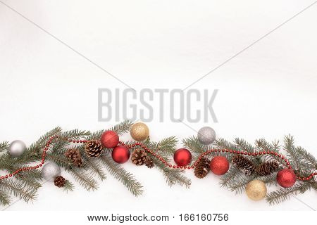 Christmas decoration with fir cone ball branch and garland on a real snow