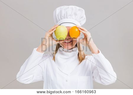 Cheerful female chef is having fun with fruit on gray background.