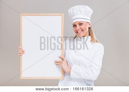Portrait of beautiful female chef holding whiteboard on gray background.