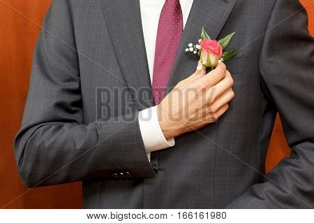 man in a gray suit corrects hand of a red rose boutonniere