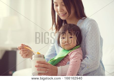 Happy Japanese Mother Feeding Her Little Cute Daughter Wih Spoon