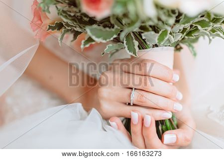Wedding bouquet of flowers in brides' hands, ring on hand