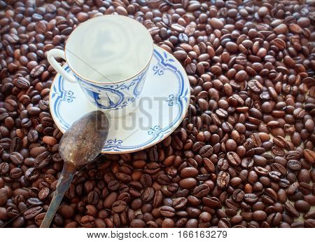 Coffee cup from thin porcelain against the background from coffee grains