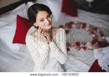 Young beautiful woman bride in hotel sitting on bed