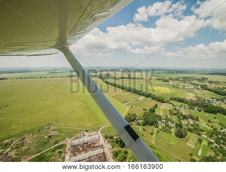 View from the pilot's seat of a small light plane while flying over the rural area