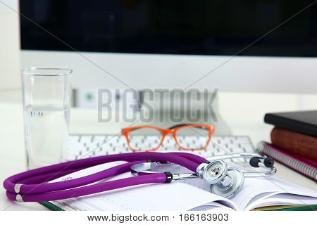 Stethoscope lying on a table on an open book.