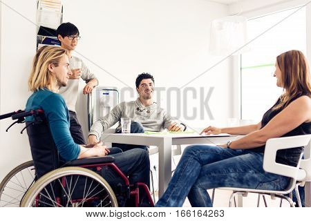office workers taking a break. one of them is sitting in a wheelchair.