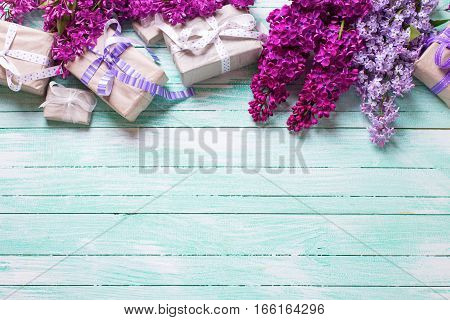 Border from gift boxes with presents and lilac flowers on turquoise wooden background. Selective focus. Place for text.