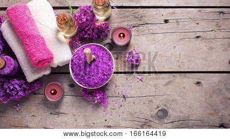 Spa concept. Sea salt candles aroma oil in bottles and towels on vintage wooden background. Selective focus. Flat lay. Place for text. Toned image.