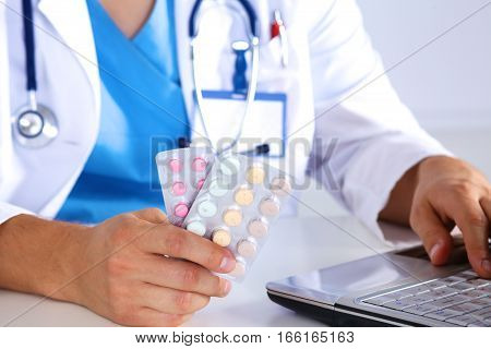 A young doctor holds the patient's hand with pills.