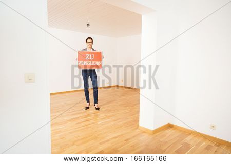 realtor in empty apartment, holding 'zu verkaufen' for sale sign
