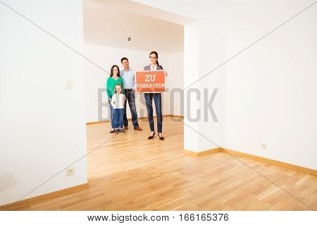 realtor and family in empty apartment, holding 'zu verkaufen' for sale sign