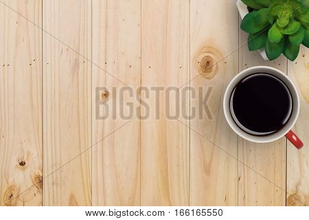 Flat lay of business copyspace workspace of office table with red cup of coffee and gree tree on vintage wooden table background.