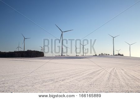 Windmill generator in wide yard / Yard of windmill power generatorunder blue sky, shown as energy industry concept