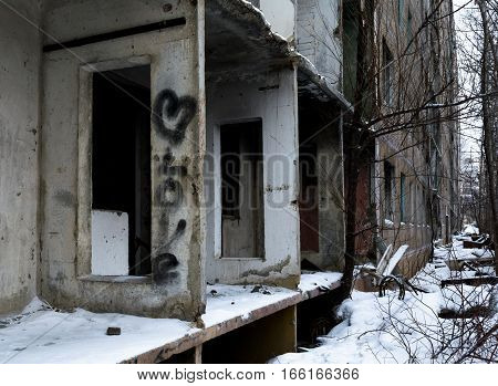 Abandoned collapsing multi-storey building. Inscription love and heart symbol on a wall. The gloom sadness loneliness.