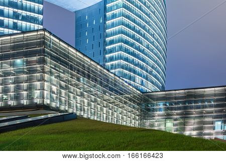 green lawn with modern illuminated office buildings background,china.