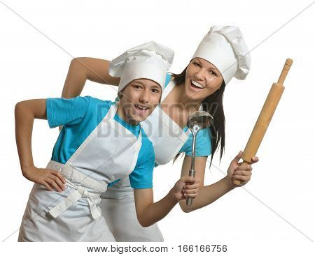 mother and son in aprons and hats posing with kitchen tools against white