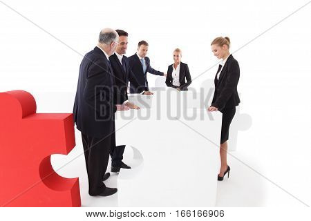 Group of business people with big jigsaw puzzle