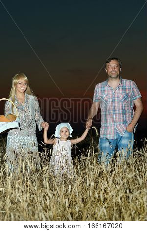 family in the meadow at night, mother, father and daughter