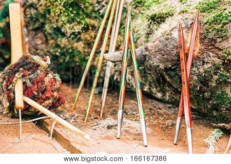 Assortment of colorful wood needles and hooks next to raw log. Concept of eco friendly knitting and crocheting shop