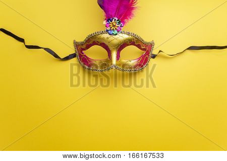 Colorful mardi gras or carnivale mask on a yellow background. Venetian masks.