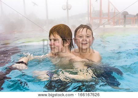 brothers are swimming in the outside area of a thermic pool in Wintertime in warm water it is foggy