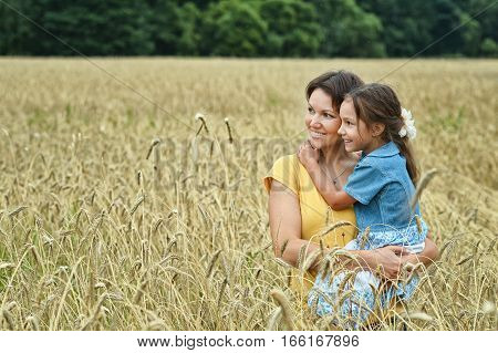 mother holding her daughter posing in the field