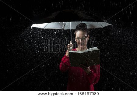 Beautiful woman with red dress reading a book in rain under an umbrella