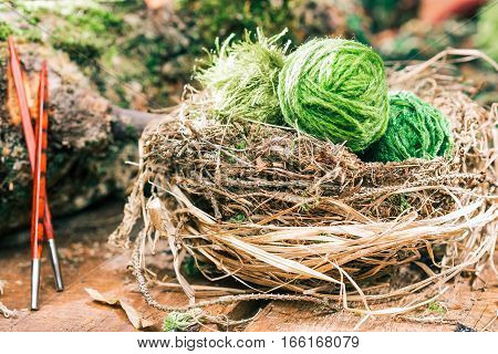 Natural bird nest of green yarn clews. Wood square section needles next to raw log. Eco friendly yarn shop concept. Selective focus