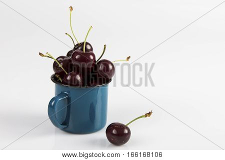 Close-up of cherries in a blue cup on a white background