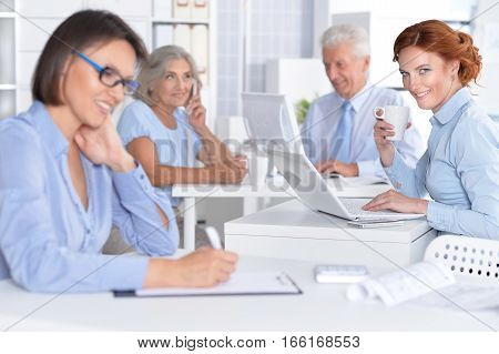 Four Businesspeople Working At Desks In Office