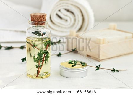 Thyme oil skincare. Bottle of herbal extract, aromatic fresh green twigs, facial cream sample jar, soft focus.