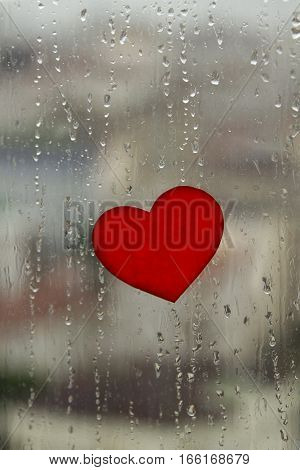 Red paper heart sticked on the wet window with rain drops