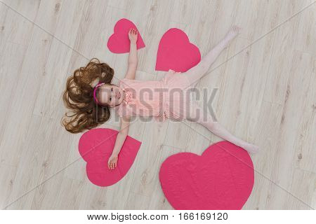 Sweet Girl Lying On The Floor With Decorations In The Form Of Heart