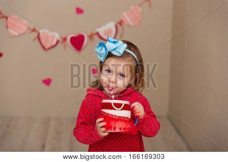 Little cute girl on the background wall of a house. The child in the scenery in the form of hearts. The kid drinks juice. Girl in a blue wrap and red dress drinks from a drink tube