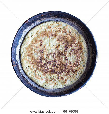 hot pancake on an old cast-iron frying pan isolated on white background top view