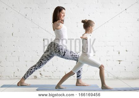 Kids yoga female teacher training a little child, practicing yoga, standing in Warrior one exercise, Virabhadrasana I pose, working out wearing sportswear, indoor full length, white studio background