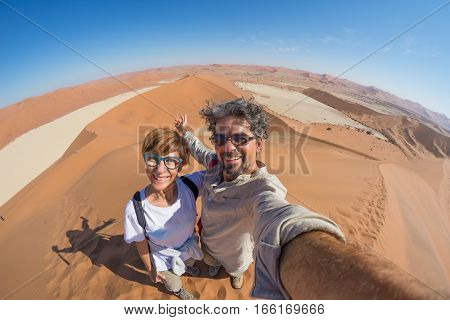 Adult couple taking selfie on sand dunes at Sossusvlei in the Namib desert Namib Naukluft National Park main travel destination in Namibia Africa. Fisheye view from above.