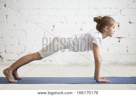 Side view of girl child practicing yoga, standing in phalankasana pose, Push ups or press ups exercise, working out wearing sportswear, t-shirt, pants, indoor full length, white loft studio background