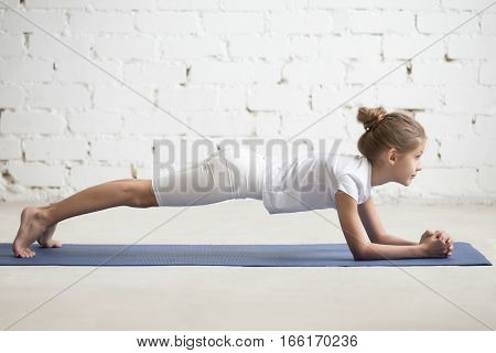 Serious girl child practicing yoga, standing in Dolphin Plank exercise, phalankasana pose working out wearing sportswear, t-shirt, pants, indoor full length, white loft studio background