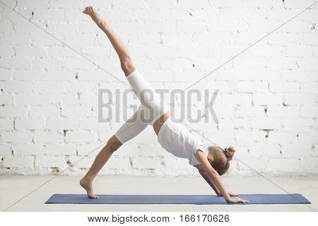 Girl child practicing yoga, standing in one legged downward facing dog exercise, eka pada adho mukha svanasana pose, working out wearing sportswear, t-shirt, pants, indoor full length, white studio