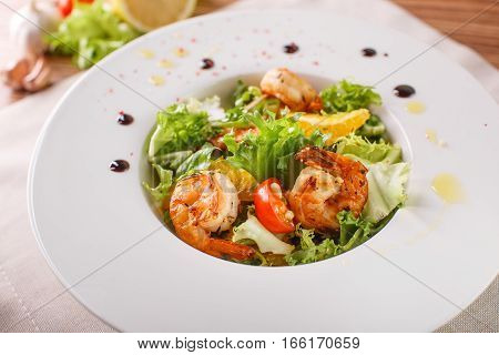 Caesar salad with shrimp on a white plate