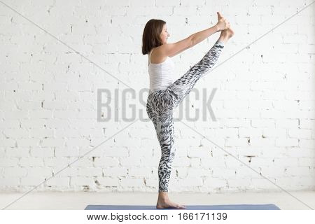 Young attractive smiling woman practicing yoga, standing in Utthita Hasta Padangustasana exercise, Extended Hand to Big Toe pose, working out wearing sportswear, full length, white studio, profile